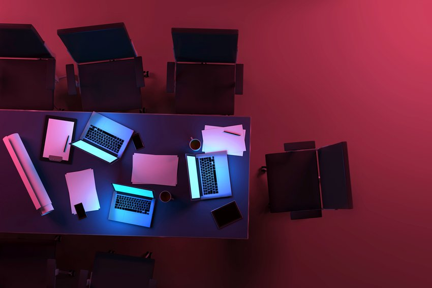 Three active laptop computers on a desk inside an office space at night, with glowing blue light from monitors illuminating the table. Aerial view, as seen from above. Purple light, in contrast with blue displays, illuminates the dark background. Teamwork and deadlines. Tablets, smartphones, coffee mugs, paper documents and projects are also visible on the desk, surrounded by office chairs. Dark purple and red hues at midnight hour. Copy space on dark areas. Digitally generated image.